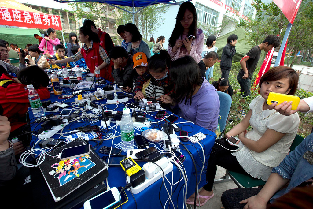 . People charge their mobile phones at a relief center in the county seat of Lushan in southwestern China\'s Sichuan province, Monday, April 22, 2013.  The tent village that sprang up in two days to house quake survivors in mountain-flanked Lushan is no ordinary refugee camp. China\'s full range of disaster response is on display: Trucks with x-ray equipment, phone-charging stations, bank tellers-on-wheels - even a tent for insurance claims. (AP Photo/Ng Han Guan)