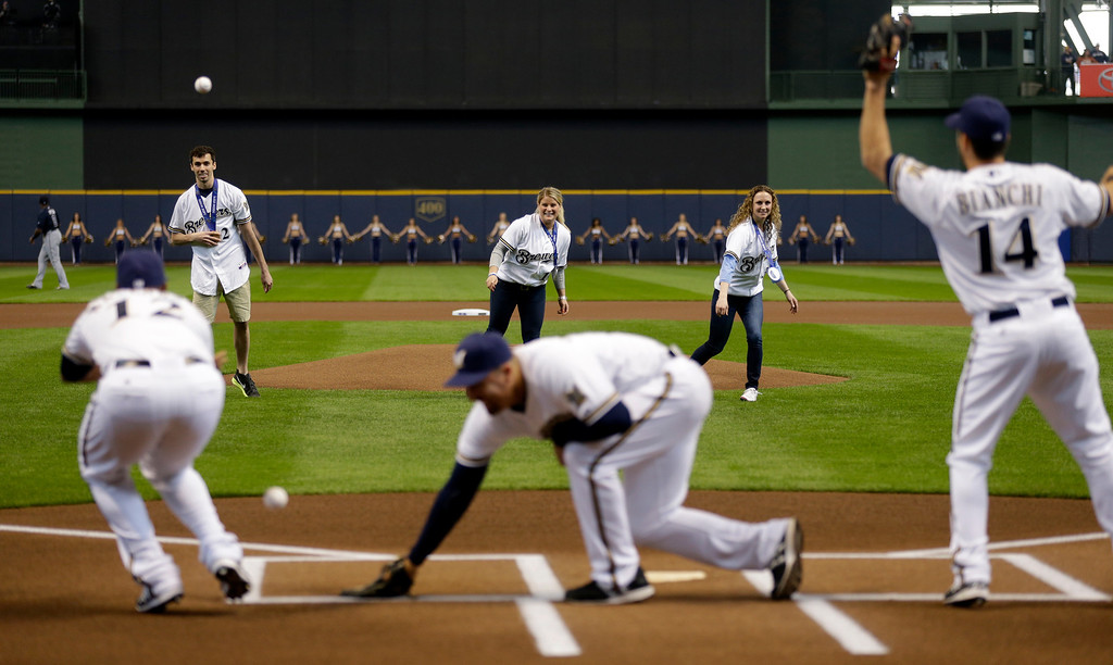 . Olympic medalists Matt Antoine, left, Brianna Decker and Jessie Vetter, right, throw out ceremonial first pitches before the opening day baseball game between the Milwaukee Brewers and Atlanta Braves at Miller Park, Monday, March 31, 2014, in Milwaukee. (AP Photo/Jeffrey Phelps)