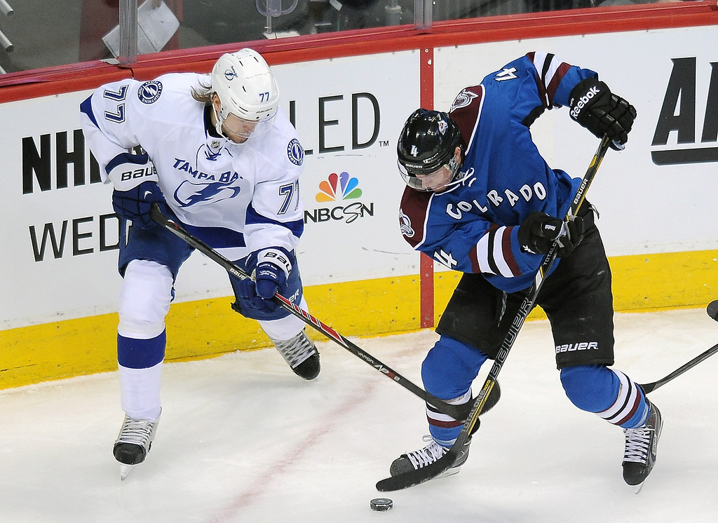 . Tampa Bay Lightning defenseman Victor Hedman, left, of Sweden, and Colorado Avalanche defenseman Tyson Barrie, right, fight for the puck in the first period of an NHL hockey game, Sunday, March 2, 2014 in Denver.  (AP Photo/Chris Schneider)