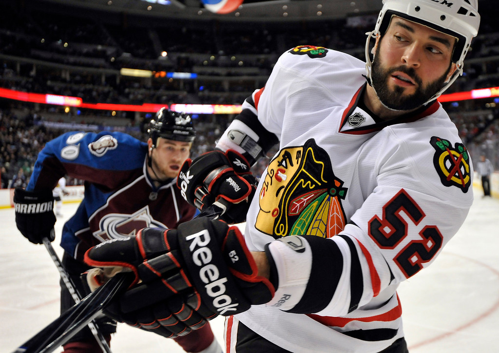 . Chicago Blackhawks left wing Brandon Bollig (52) and Colorado Avalanche center Ryan O\'Reilly (90) skate during the second period of an NHL hockey game, Monday, March 18, 2013, in Denver. (AP Photo/Jack Dempsey)