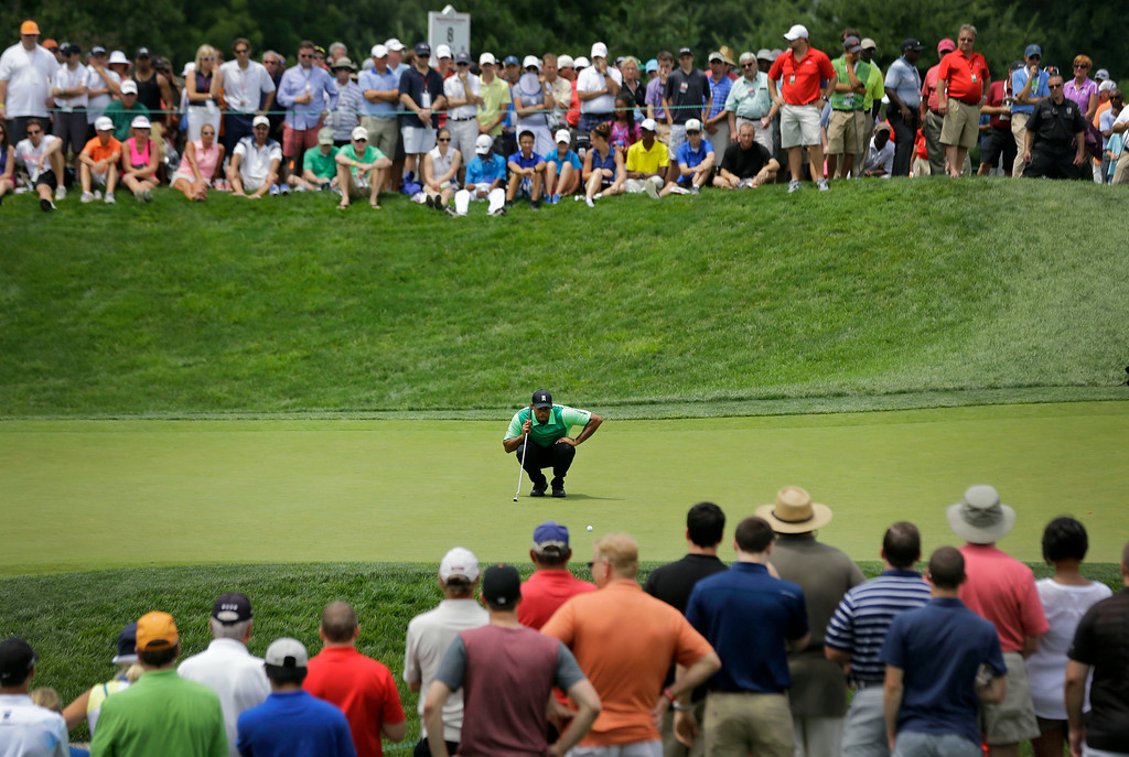 . Tiger Woods examines his putt on the seventh green during the first round of the Quicken Loans National PGA golf tournament, Thursday, June 26, 2014, in Bethesda, Md. (AP Photo/Patrick Semansky)