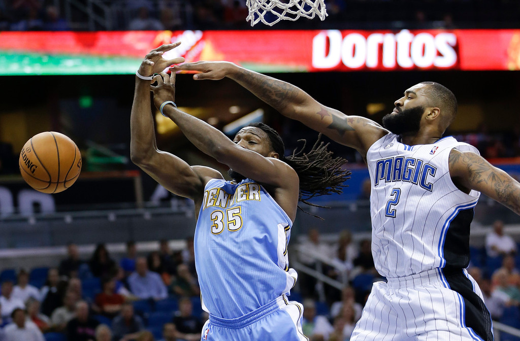 . Orlando Magic\'s Kyle O\'Quinn (2) blocks a shot by Denver Nuggets\'s Kenneth Faried (35) during the first half of an NBA basketball game in Orlando, Fla., Wednesday, March 12, 2014. (AP Photo/John Raoux)