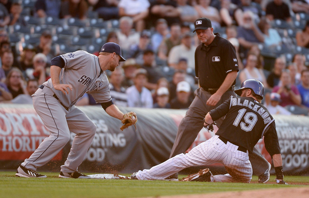 . Colorado Rockies center fielder Charlie Blackmon (19) slides under the tag of San Diego Padres third baseman Chase Headley (7) after a ground out hit by Colorado Rockies first baseman Justin Morneau (33) July 8, 2014 at Coors Field. (Photo by John Leyba/The Denver Post)