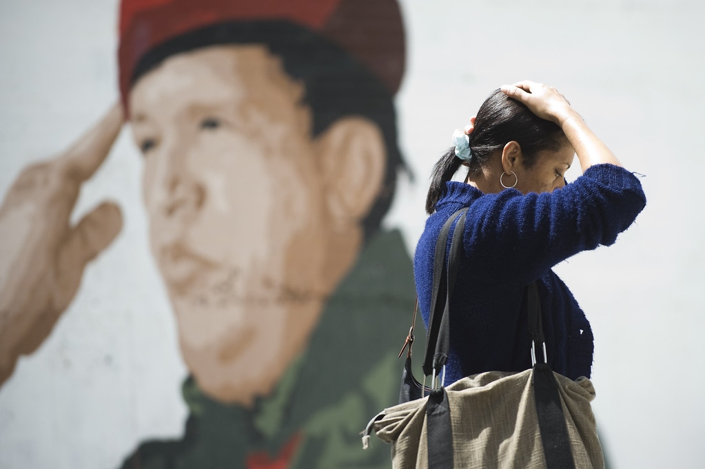 . A woman passes by a graffiti depicting Venezuelan President Hugo Chavez, in Caracas on May 16, 2012. President Hugo Chavez passed away on March 5, 2013 in Caracas after a long fight with cancer, Venezuelan Vice President Nicolas Maduro announced. LEO RAMIREZ/AFP/Getty Images