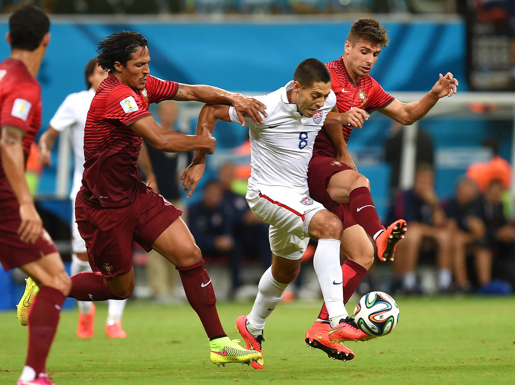 . United States\' Clint Dempsey, centre, is challenged by Portugal\'s Bruno Alves, left, and Portugal\'s Miguel Veloso, right, during the group G World Cup soccer match between the USA and Portugal at the Arena da Amazonia in Manaus, Brazil, Sunday, June 22, 2014. (AP Photo/Paulo Duarte)