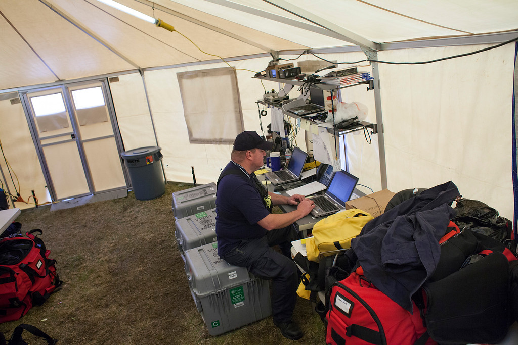 . Brett Bigger works inside of a communications tent at the FEMA Washington State Task Force 1 base camp on March 27, 2014 in Darrington, Washington.  (Photo by David Ryder/Getty Images)