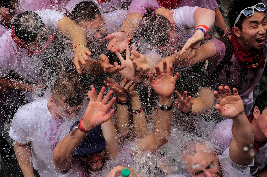 ". Revelers enjoy water being thrown from a balcony during the launch of the \'Chupinazo\' rocket, to celebrate the official opening of the 2014 San Fermin fiestas, in Pamplona, Spain, Sunday, July 6, 2014. Revelers from around the world kick off the festival with a messy party in the Pamplona town square, one day before the first of eight days of the running of the bulls glorified by Ernest Hemingway\'s 1926 novel ""The Sun Also Rises.\"" (AP Photo/Alvaro Barrientos)"