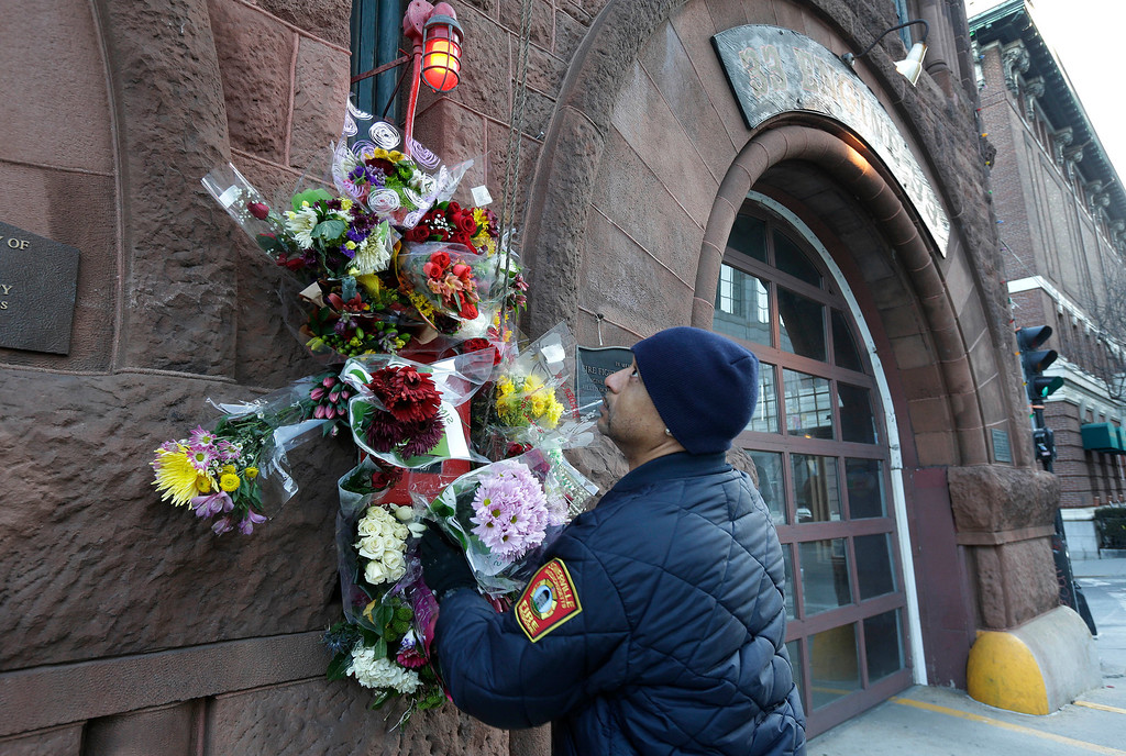 . Somerville, Mass. firefighter Earl Johnson places flowers at a makeshift memorial on the front of fire station Engine 33, Thursday, March 27, 2014, in Boston. Fire station Engine 33 was the station of fallen firefighters Lt. Edward J. Walsh and Michael R. Kennedy who lost their lives fighting a 9-alarm fire in a four-story brownstone in Boston\'s Back Bay neighborhood Wednesday, March 26, 2014. (AP Photo/Steven Senne)