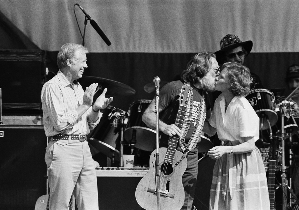 ". Singer Willie Nelson and Rosalynn Carter, wife of former President Jimmy Carter embrace on stage following the singing of ""Amazing Grace,\"" May 18, 1985 in Plains Ga., while the former president applauds at Nelson\'s Plains Centennial Concert. (AP Photo/Ric Feld)"