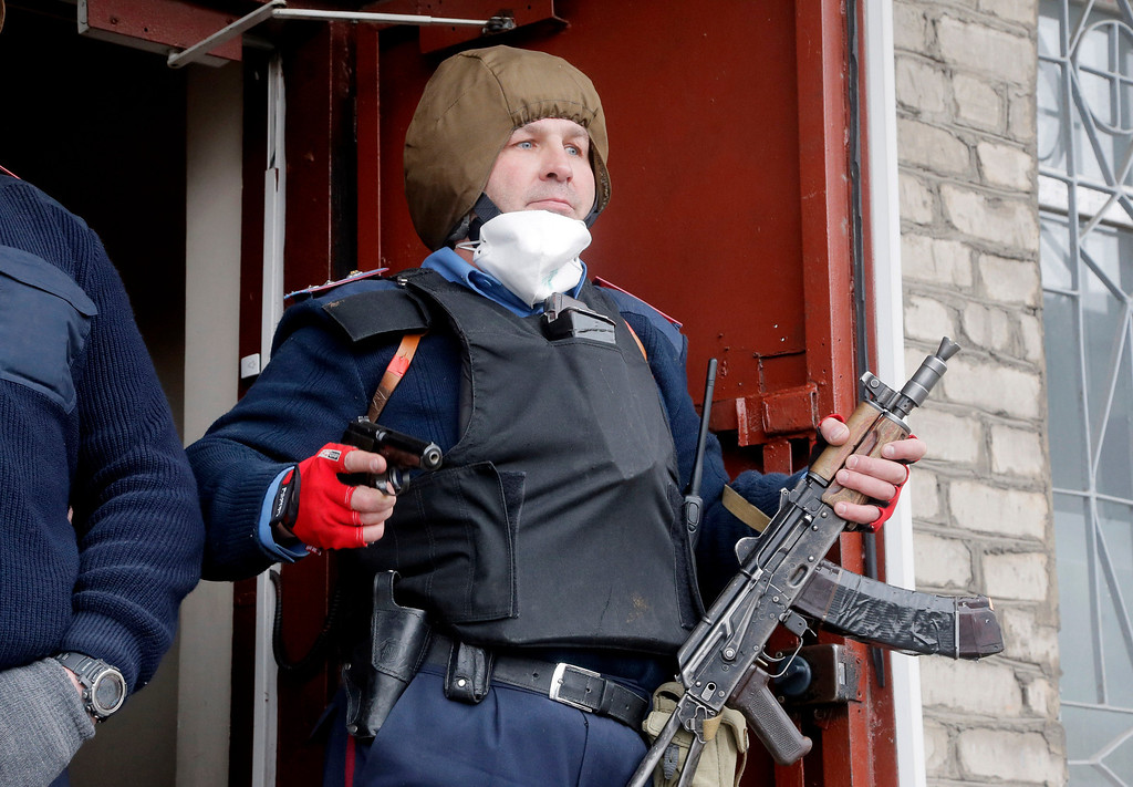 . The head of the local police station Herman Pristupa, brandishes firearms at the entrance to a police headquarters stormed by pro-Russian activists in Horlivka, Ukraine, Monday, April 14, 2014. (AP Photo/Efrem Lukatsky)