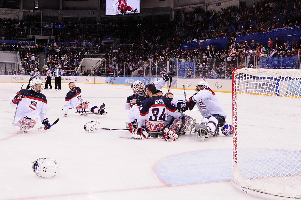 . The team of the United States of America celebrates after the ice sledge hockey gold medal game between the Russian Federation and the United States of America at the Shayba Arena during day eight of the 2014 Paralympic Winter Games on March 15, 2014 in Sochi, Russia.  (Photo by Dennis Grombkowski/Getty Images)