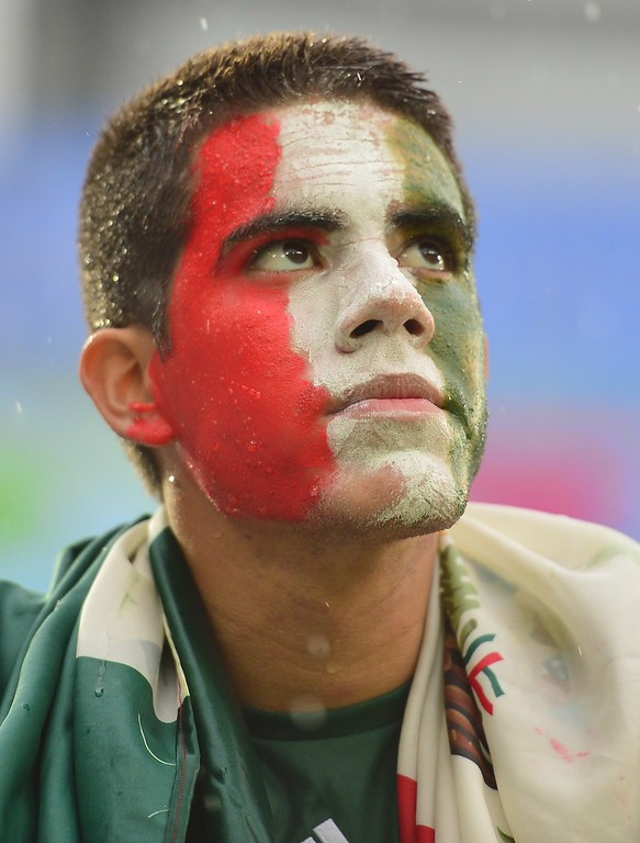 . A Mexican football fan waits for the start of a Group A football match between Mexico and Cameroon at the Dunas Arena in Natal during the 2014 FIFA World Cup on June 13, 2014.  AFP PHOTO / YURI  CORTEZ/AFP/Getty Images