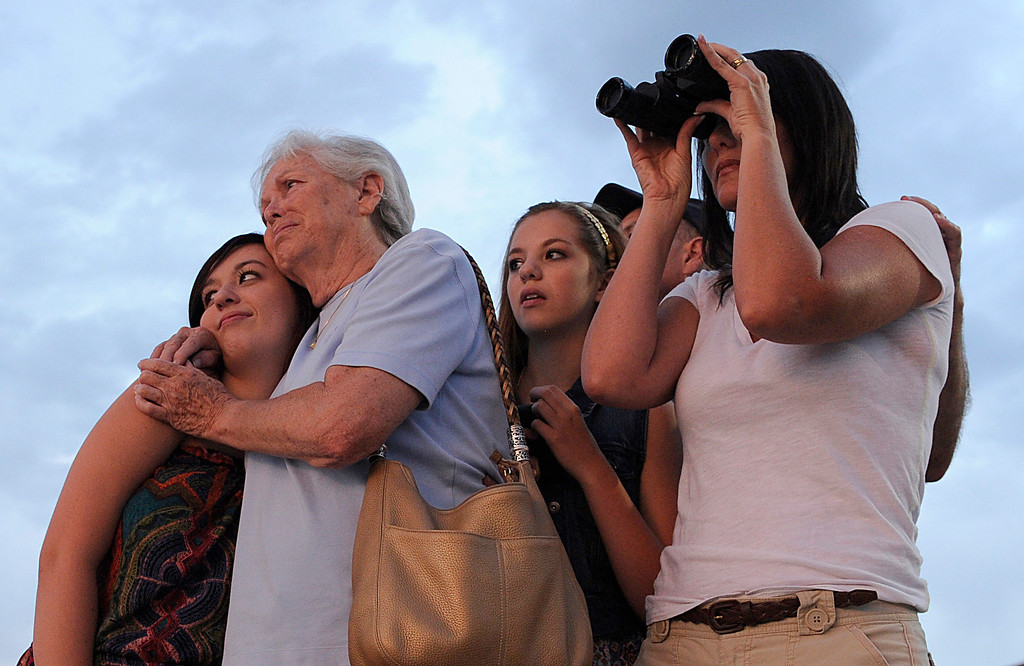. Faye Courtland hugs her granddaughter Emily Parker, left, as her daughter Laura, granddaughter Katye and husband Tom Courtland watched the smoke plumes west of town Wednesday night. The Parker family was on vacation when the fire started and have not been able to return to their home. The Waldo Canyon fire continued to burn in the hills above Colorado Springs Wednesday night, June 27, 2012. Karl Gehring/The Denver Post