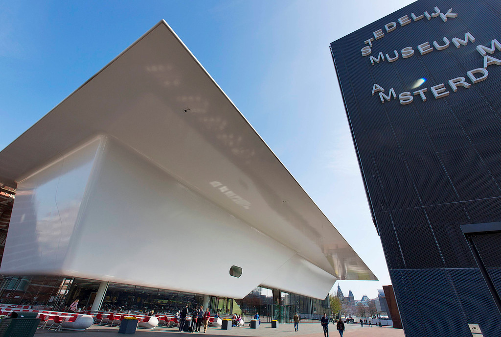 . People pass the recently rennovated Stedelijk Museum with a new wing that resembles a giant white bath tub on the Museum square in Amsterdam April 24, 2013. The Royal celebrations in the Netherlands this week put the country and the capital Amsterdam on front pages and television screens around the world with an orange splash. There\'s plenty to see and do in 48 hours in this compact city, where the world-famous Rijksmuseum only recently reopened after an extensive renovation. Picture taken April 24, 2013. REUTERS/Michael Kooren