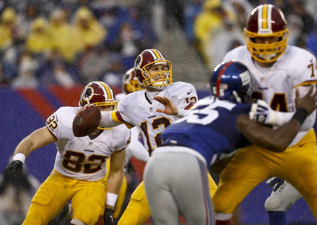 . Kirk Cousins #12 of the Washington Redskins looks for an open man against the New York Giants during their game at MetLife Stadium on December 29, 2013 in East Rutherford, New Jersey.  (Photo by Jeff Zelevansky/Getty Images)