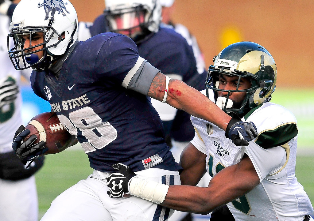 . Utah State\'s Joey DeMartino (28) runs the ball as Colorado State\'s Trent Matthews attempts to make a tackle during an NCAA college football game, Saturday, Nov. 23, 2013, in Logan, Utah. Utah State won 13-0. (AP Photo/Herald Journal, John Zsiray)