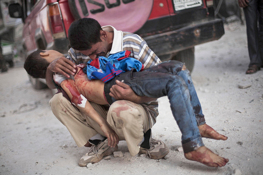 . FILE - A Syrian man cries while holding the body of his son, killed by the Syrian Army, near Dar El Shifa hospital in Aleppo, Syria, Wednesday, Oct. 3, 2012. (AP Photo/Manu Brabo, File)
