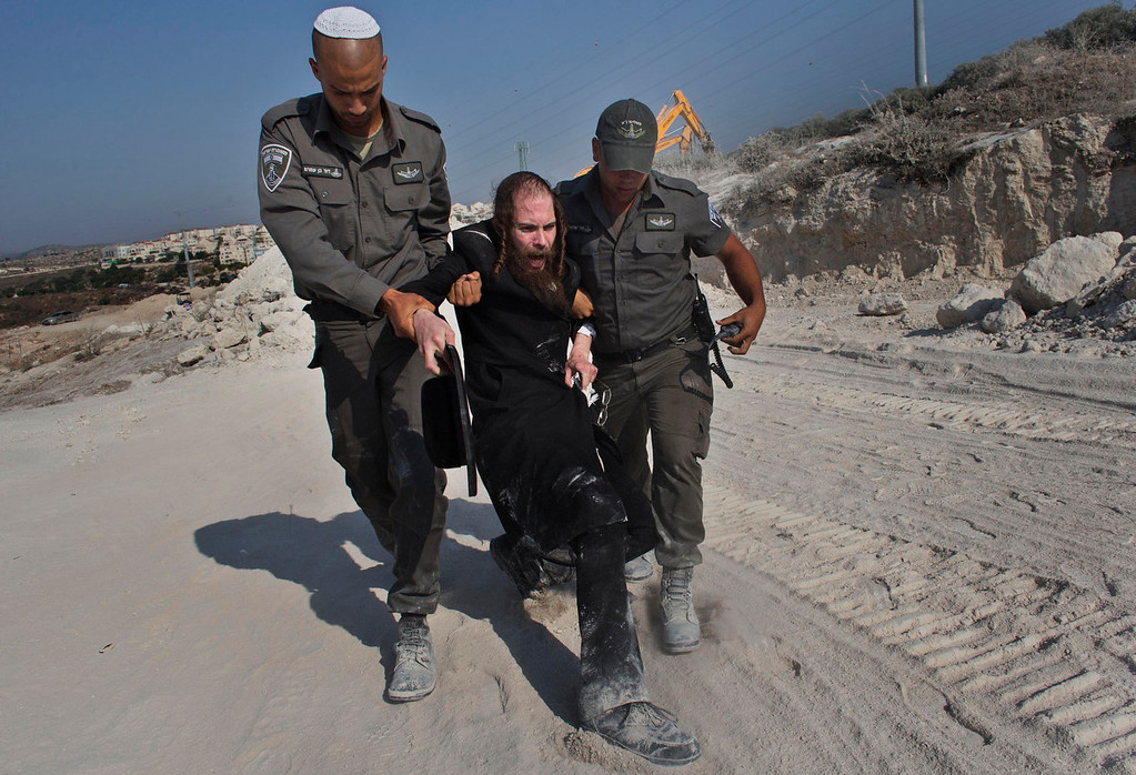 . An ultra-Orthodox Jewish protester is dragged by Israeli border police on a construction site in Ramat Beit Shemesh, Israel, Wednesday, Aug. 14, 2013. A group of ultra-Orthodox Jews claim ancient graves will be desecrated during the construction of a new housing project. (AP Photo/Bernat Armangue)