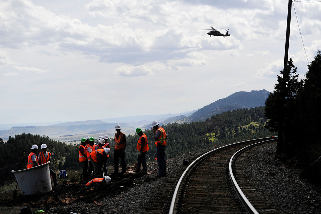 . ELDORADO SPRINGS, CO - SEPTEMBER 18: A military helicopter flies over a fiber optics crew working  to repair damage from recent flooding along Union Pacific Railroad tracks  just a few miles southwest of the town of Eldorado Springs Colorado Wednesday afternoon, September 18, 2013. (Photo By Andy Cross/The Denver Post)