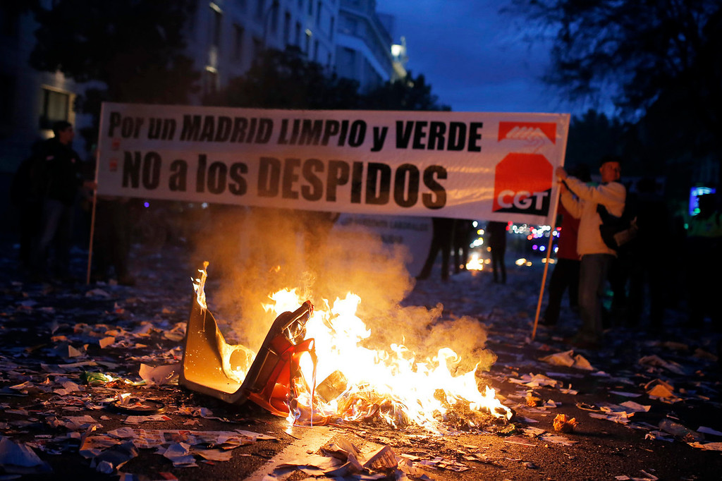 ". Protestors burn trash as they carry a banner reading ""Madrid clean and green. No layoffs!\"" during a demonstration against layoffs of street cleaners and garbage collectors in Madrid, Spain, Monday, Nov. 4, 2013. Trash collectors in Madrid have started bonfires and set off firecrackers during a noisy protest in one of the Spanish capitalís main squares as they prepare to start an open-ended strike. (AP Photo/Andres Kudacki)"