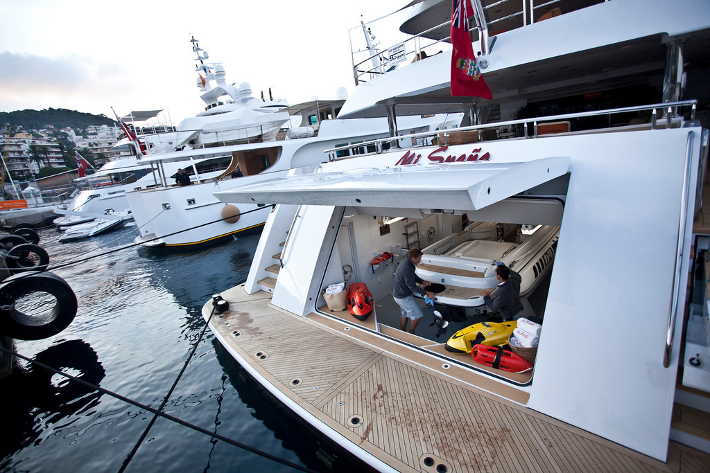 . Crew members clean a tender boat as it sits stowed onboard the 190ft (57.9m) motor yacht Mi Sueno, manufactured by Trinity Yachts LLC, in the harbor in Nice, France, on Wednesday, Sept. 25, 2013.  Photographer: Balint Porneczi/Bloomberg