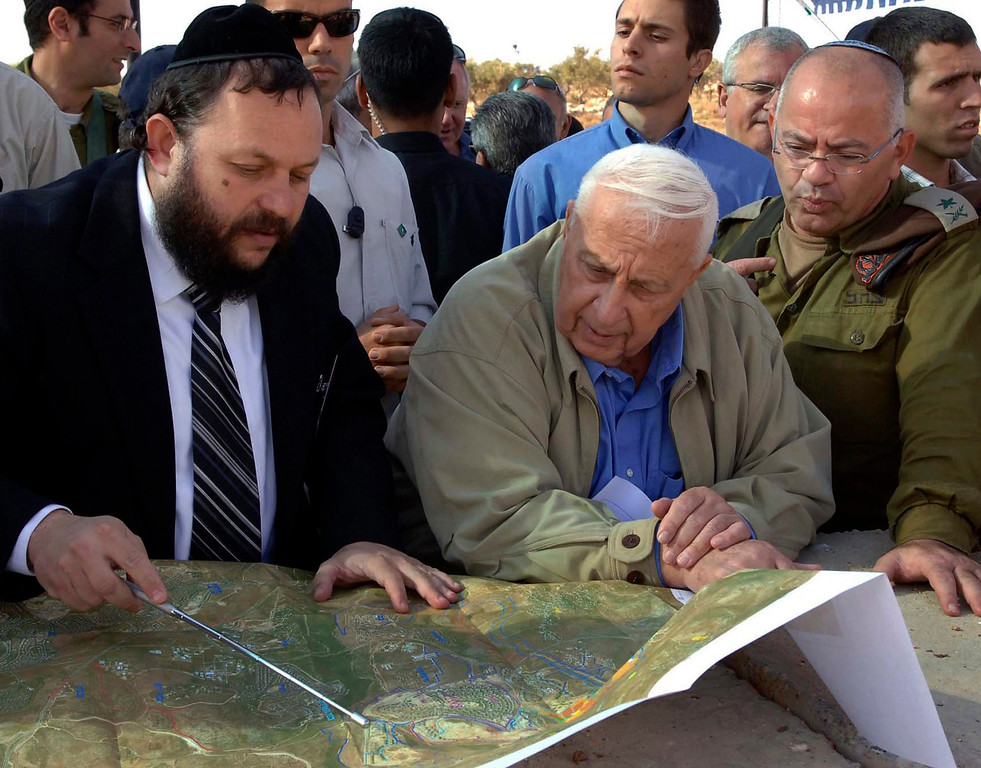 . A file handout photograph dated 08 November 2005 and supplied by the Israeli Government Press Office shows then Israeli Prime Minister Ariel Sharon (C) as he is briefed by an unidentified man on the state of construction of the \'separation fence\', or wall, being built around Jerusalem, Israel.  EPA/ISRAELI GOVERNMENT PRESS OFFICE