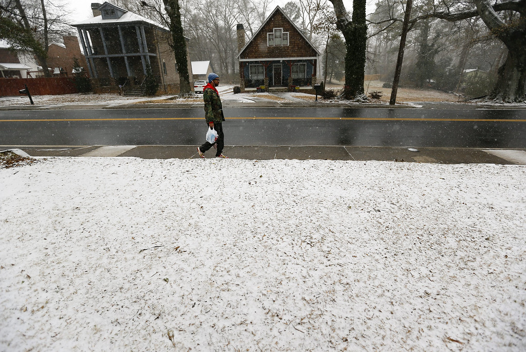. Tobias Maines walks home with last minute groceries as a winter storm affects Atlanta, Georgia, USA, 28 January 2014. Several inches of snow were expected in parts of the southern United States.  EPA/ERIK S. LESSER