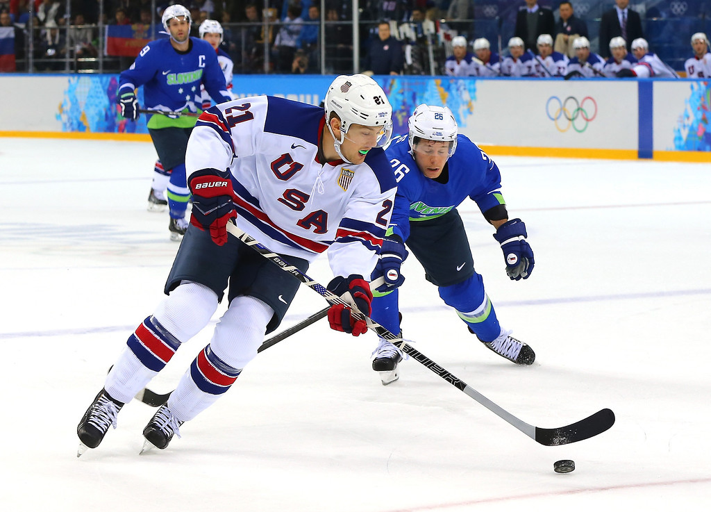 . James van Riemsdyk #21 of the United States handles the puck against Jan Urbas #26 of Slovenia in the first period during the Men\'s Ice Hockey Preliminary Round Group A game on day nine of the Sochi 2014 Winter Olympics at Shayba Arena on February 16, 2014 in Sochi, Russia.  (Photo by Martin Rose/Getty Images)