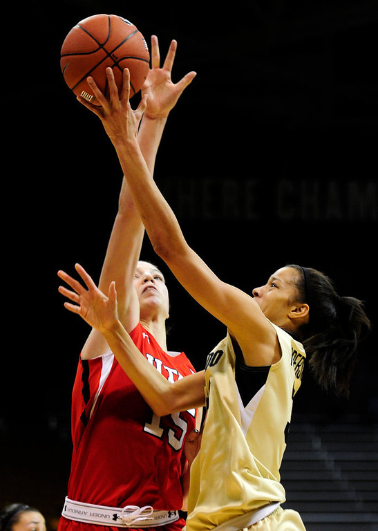 . Colorado\'s Arielle Roberson (right) takes a shot while under pressure from Utah\'s Michelle Plouffe (left) during their basketball game at the University of Colorado in Boulder , Colorado January 8, 2013. BOULDER DAILY CAMERA/ Mark Leffingwell