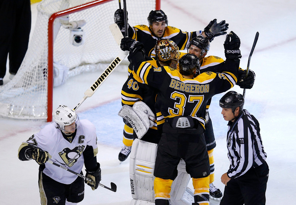 . The Boston Bruins celebrate their win as Pittsburgh Penguins\' Sidney Crosby (L) skates away in Game 4 of their NHL Eastern Conference finals hockey playoff series in Boston, Massachusetts, June 7, 2013. REUTERS/Brian Snyder