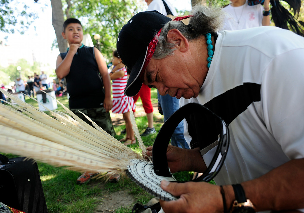 . Raul Chavez, co-captain of the Huitzilopochtli Traditional Aztec Dance Group, prepares a Penacho prior to the group\'s performance during the A Taste of Colorado festival at Civic Center Park in Denver, Colorado,Saturday, August 30, 2014. (Photo By Brenden Neville / Special to The Denver Post)