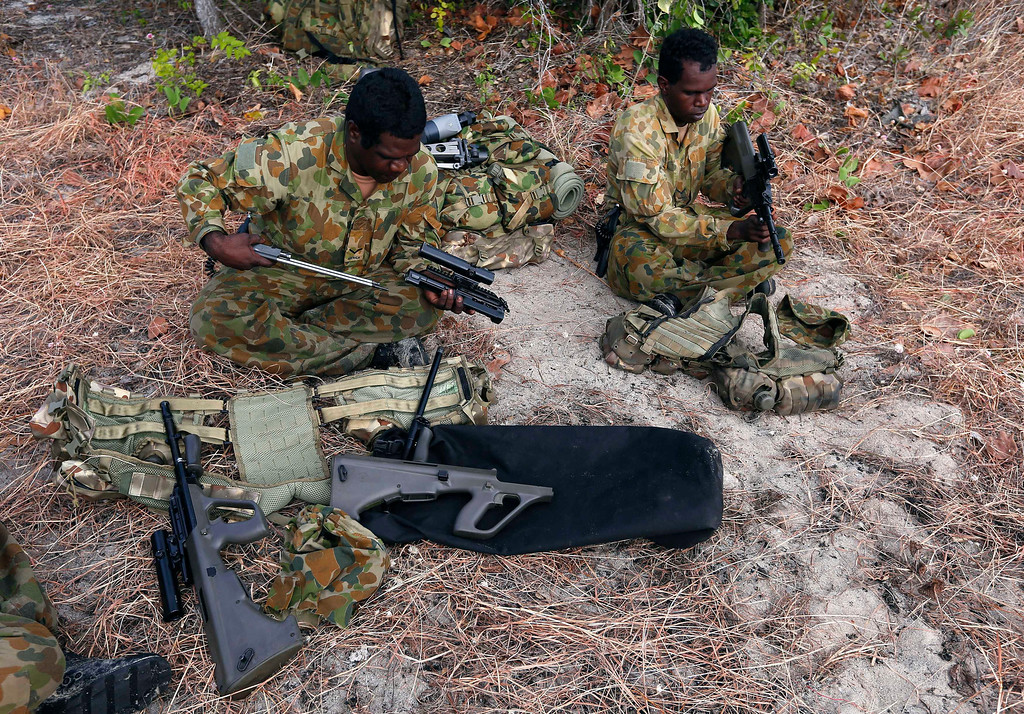 . Lance-corporal Danny Daniels (L) and Private Jonah Thingle, indigenous soldiers from Australia\'s North West Mobile Force (NORFORCE) unit, clean their F88 Austeyr rifles after a surveillance and reconnaissance patrol around Astell Island, part of the English Company Islands, located inside Arnhem Land in the Northern Territory July 17, 2013. NORFORCE is a surveillance unit that employs ancient Aboriginal skills to help in the seemingly impossible task of patrolling the country\'s vast northwest coast. NORFORCE\'s area of operations is about 1.8 million square km (700,000 square miles), covering the Northern Territory and the north of Western Australia. Aboriginal reservists make up a large proportion of the 600-strong unit, and bring to bear their knowledge of the land and the food it can provide. Fish, shellfish, turtle eggs and even insects supplement rations during the patrol, which is on the lookout for illegal foreign fishing vessels and drug smugglers, as well as people smugglers from neighboring Indonesia. Picture taken July 17, 2013.   REUTERS/David Gray
