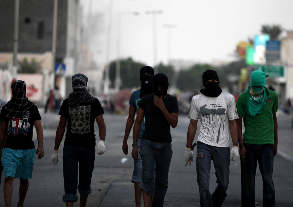 ". Masked Bahraini anti-government protesters walk away from a barricade as blocking a street in the western village of Malkiya, Bahrain, Tuesday, Aug. 13, 2013. Inspired by the movement behind Egypt\'s military coup, pro-democracy activists in Bahrain are hoping to gain new momentum by calling for nationwide protests Wednesday. Authorities warned they will ""forcefully confront\"" any large demonstrations, raising fears of more violence in the strategic Gulf kingdom. (AP Photo/Hasan Jamali)"