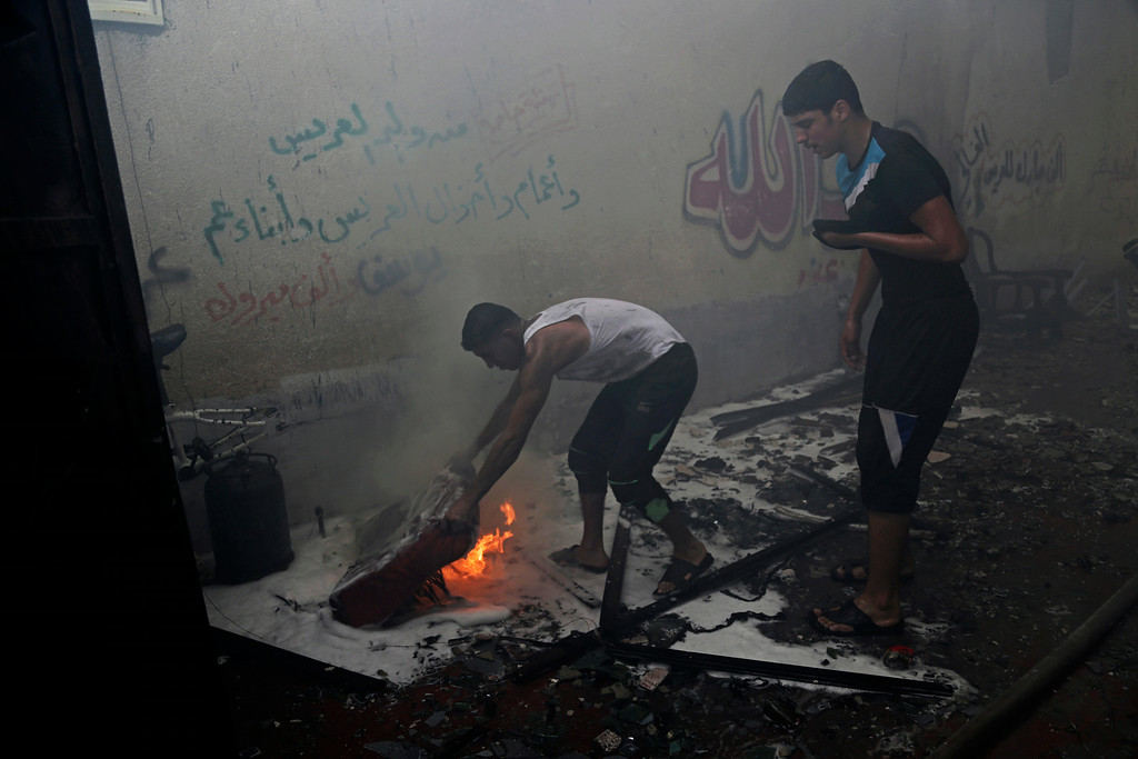 ". Palestinians extinguish a fire following an Israeli strike on a building in Gaza, northern Gaza Strip, Saturday, Aug. 23, 2014. Arabic writing on wall gives congratulations from relatives on a wedding, ""a thousand congratulations.\"" (AP Photo/Adel Hana)"