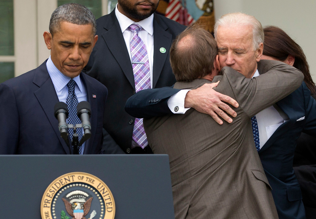 . President Barack Obama stands at the podium at left as Mark Barden, the father of Newtown shooting victim Daniel is embraced by Vice President Joe Biden during a news conference in the Rose Garden of the White House, Wednesday, April 17, 2013, in Washington, about measures to reduce gun violence. (AP Photo/Carolyn Kaster)