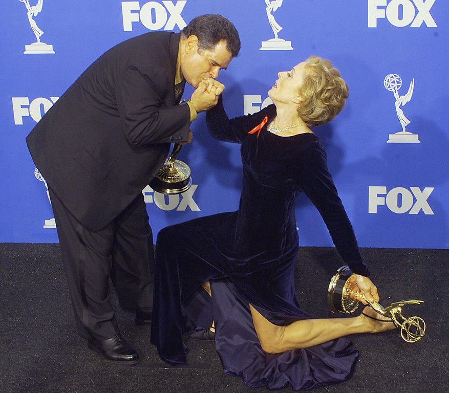 ". Actors Michael Badalucco (L) kisses the hand of co-star Holland Taylor (R) as they pose with their Emmy Award for Outstanding Supporting Actor and Actress for a Drama Series for their roles in ""The Practice\"" at the 51st Emmy Awards at the Shrine Auditorium in Los Angeles 12 September, 1999.  Scott Nelson/AFP/Getty Images"