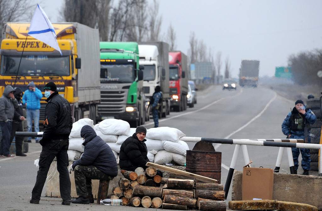 . Armed masked men who call  themselves members of Ukraine\'s disbanded elite Berkut riot police force and local militiamen check vehicles at their checkpoint on a highway that connect Black Sea Crimea  peninsula to mainland Ukraine near the city of Armyansk, on February 28, 2014.  AFP PHOTO / VIKTOR DRACHEV/AFP/Getty Images