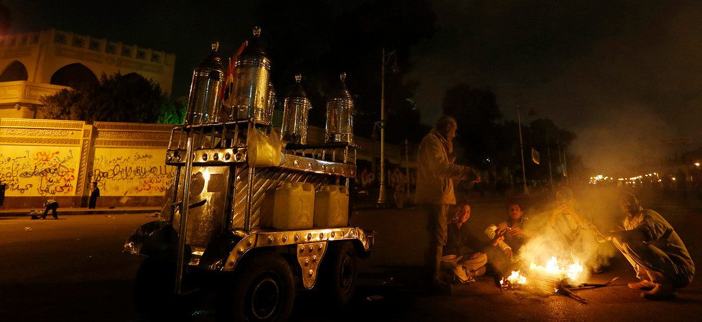 . Protesters make a bonfire in front of the presidential palace, background, in Cairo, Egypt, Sunday, Dec. 9, 2012. Egypt\'s liberal opposition called for more protests Sunday, seeking to keep up the momentum of its street campaign after the president made a partial concession overnight but refused its main demand he rescind a draft constitution going to a referendum on Dec. 15. (AP Photo/Petr David Josek)
