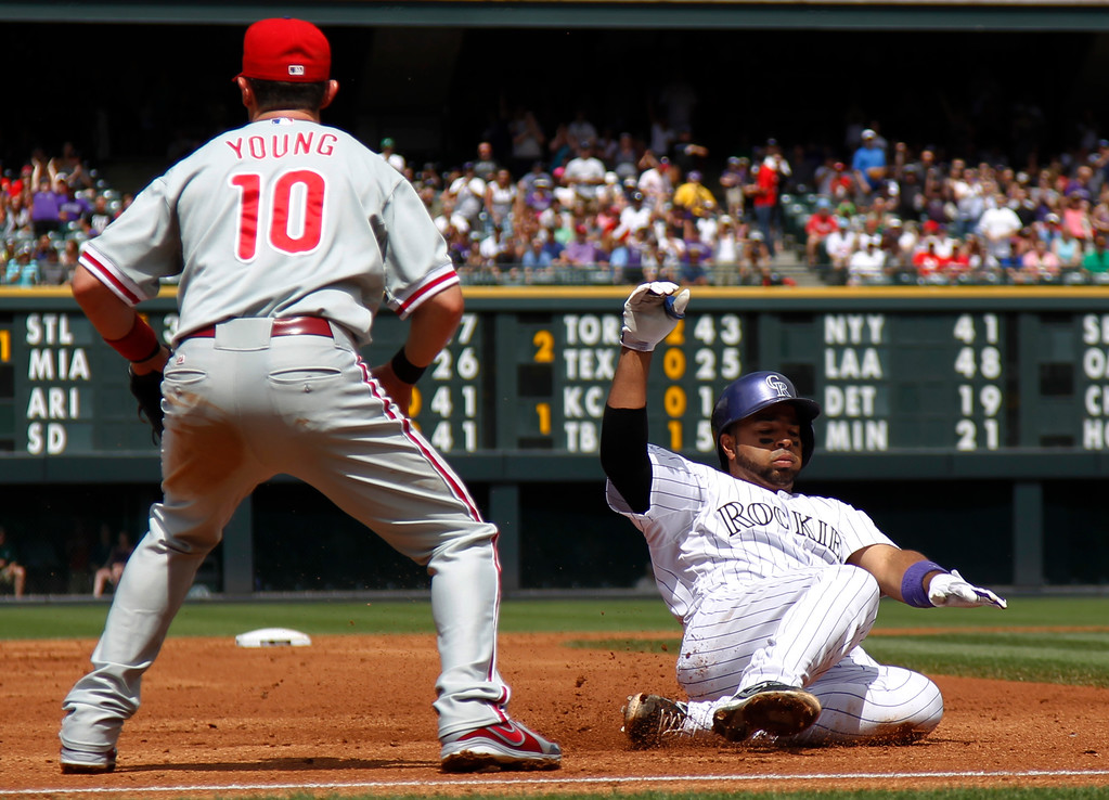 . Colorado Rockies\' Wilin Rosario, right, slides into third base after hitting an RBI-triple as Philadelphia Phillies third baseman Michael Young waits for the throw from the outfield in the first inning of a baseball game in Denver, Saturday, June 15, 2013. (AP Photo/David Zalubowski)