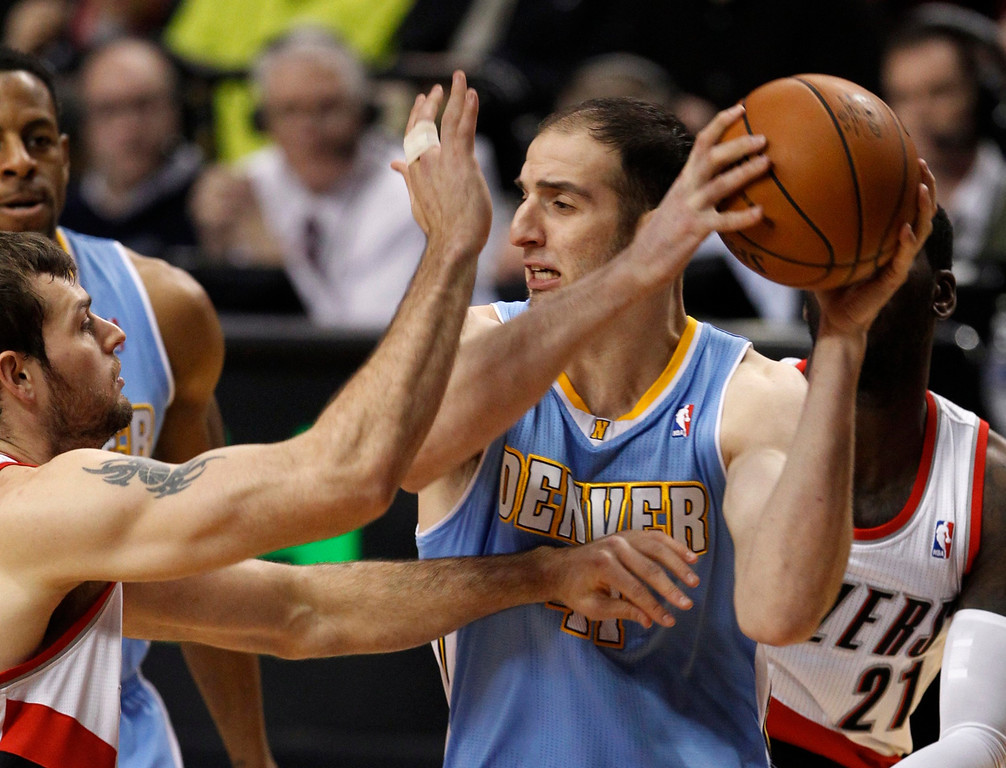 . Denver Nuggets center Kosta Koufos (R) looks to pass as Portland Trail Blazers power forward Joel Freeland (L) defends during first quarter of their NBA basketball game in Portland, Oregon, December 20, 2012.  REUTERS/Steve Dipaola
