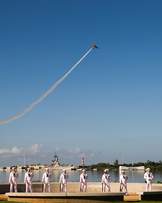 . A vintage WWII airplane files over the USS Arizona at the ceremony commemorating the 72nd anniversary of the attack on Pearl Harbor, Saturday, Dec. 7, 2013, in Honolulu.  (AP Photo/Marco Garcia)