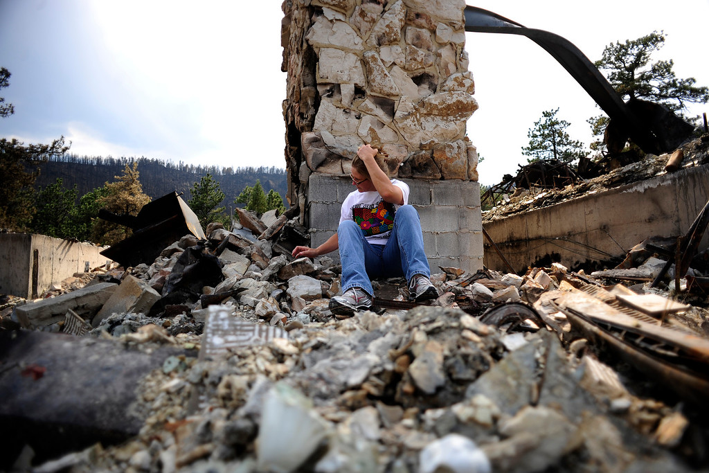 . Lucinda Able sits amidst the burned ruins of her parents\' home on Stove Prairie Road on Sunday, July 1, 2012. Lucinda and her parents were visiting the home for the first since it was burned by the High Park Fire. AAron Ontiveroz, The Denver Post.