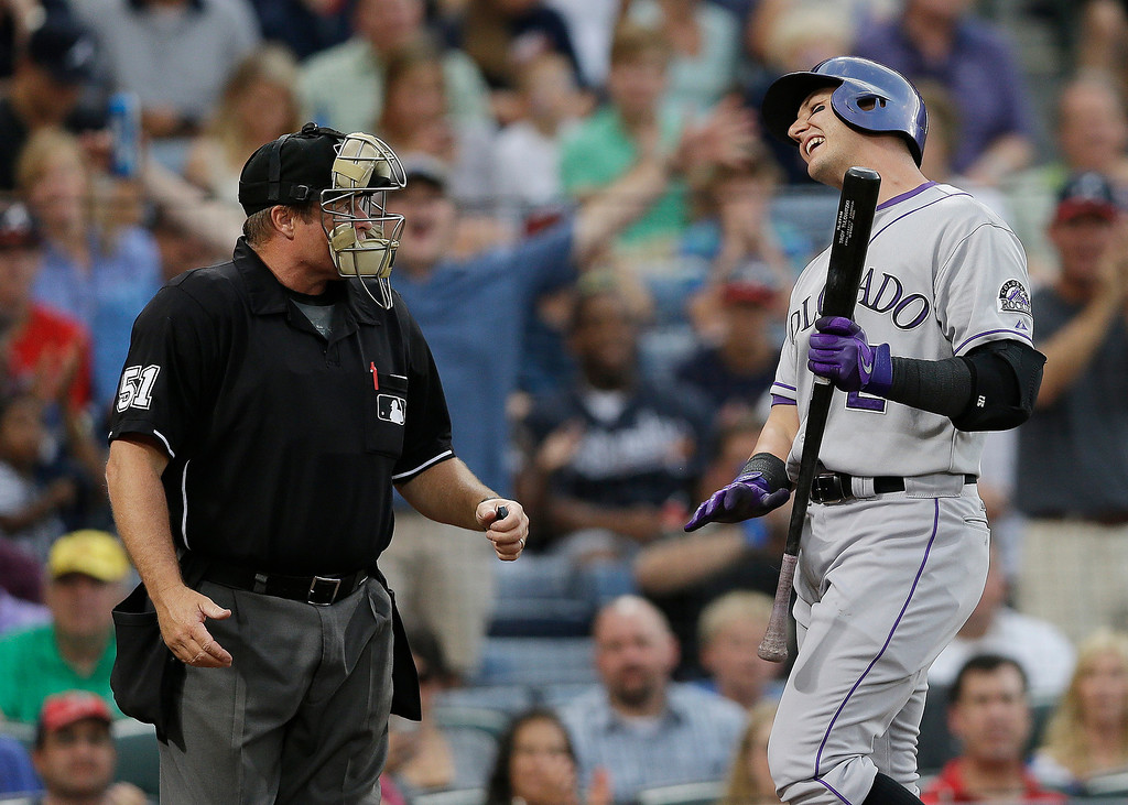. Colorado Rockies\' Troy Tulowitzki argues with umpire Marvin Hudson, left, after striking out in the second inning of a baseball game against the Atlanta Braves in Atlanta, Thursday, Aug. 1, 2013. (AP Photo/John Bazemore)