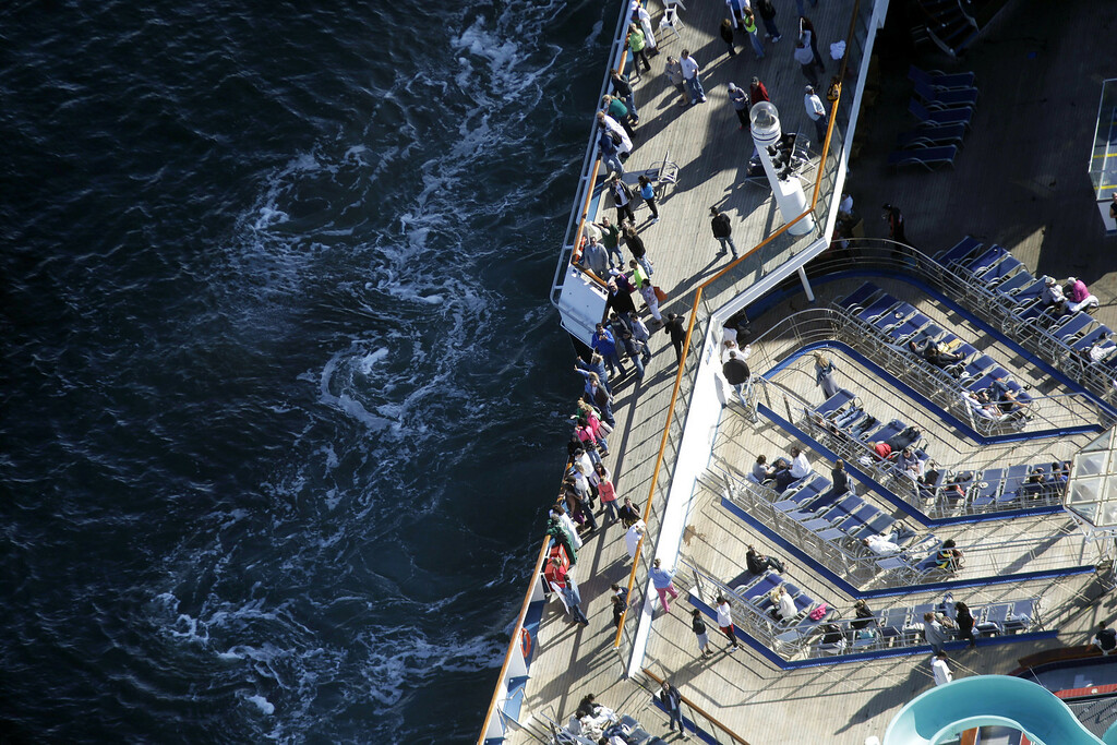 . Passengers stand on the upper deck of the disabled Carnival Lines cruise ship Triumph as it is towed to harbor off Mobile Bay, Ala., Thursday, Feb. 14, 2013. (AP Photo/Gerald Herbert)