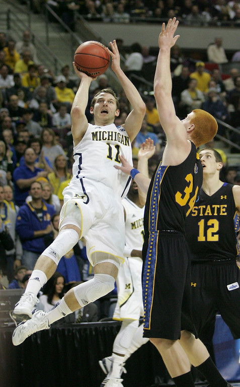 . Michigan Wolverines\' Nik Stauskas takes an off balance shot against South Dakota State Jackrabbits\' Tony Fiegen during first-half action in the men\'s NCAA basketball tournament at The Palace of Auburn Hills in Auburn Hills, Michigan, Thursday, March 21, 2013. (Kirthmon F. Dozier/Detroit Free Press/MCT)