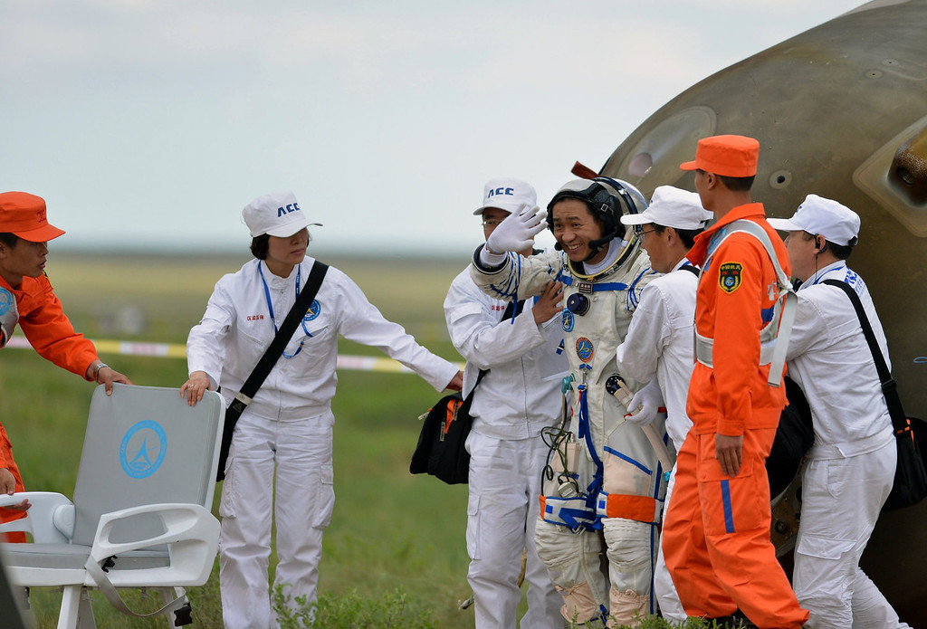 . Chinese astronaut Nie Haisheng (4th R) gets out out of the Shenzhou-10 spacecraft that landed on the grasslands of north China\'s Inner Mongolia region on June 26, 2013, after a 15-day mission in space. China completed its longest manned space mission on June 26 as its Shenzhou-10 spacecraft and three crew members safely returned to Earth, in a major step towards Beijing\'s goal of building a permanent space station by 2020.  AFP PHOTOSTR/AFP/Getty Images