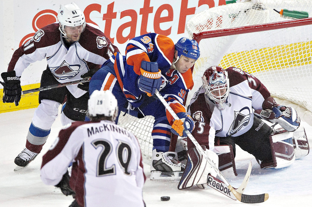 . Colorado Avalanche goalie Jean-Sebastien Giguere (35) makes the save on Edmonton Oilers\' Ryan Smyth (94) as Andre Benoit (61) and Nathan MacKinnon (29) chase the rebound during second period NHL hockey action in Edmonton, Alberta, on Tuesday April 8, 2014. (AP Photo/The Canadian Press, Jason Franson)