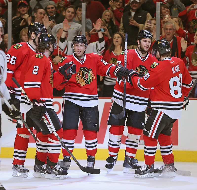 . CHICAGO, IL - DECEMBER 27: (L-R) Duncan Kieth #2, Michal Handzus #26, Kris Versteeg #23, Brent Seabrook #7 and Patrick Kane #88 of the Chicago Blackhawks celebrate Versteeg\'s second period goal against the Colorado Avalanche at the United Center on December 27, 2013 in Chicago, Illinois. (Photo by Jonathan Daniel/Getty Images)