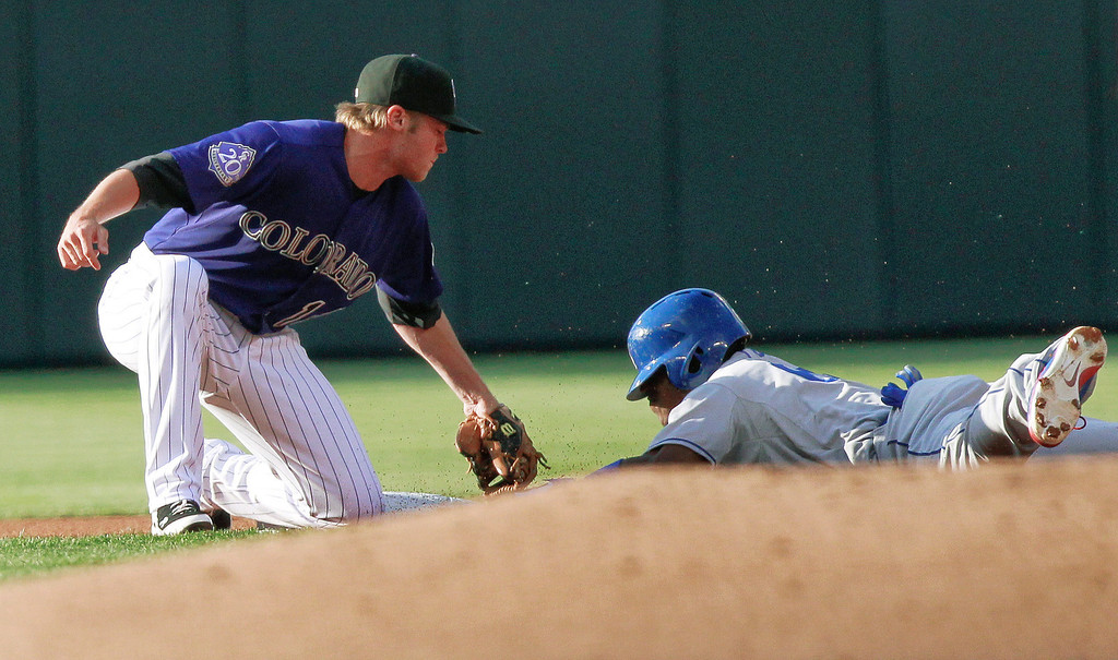 . Los Angeles Dodgers\' Yasiel Puig, right, is caught stealing by Colorado Rockies\' Josh Rutledge during the first inning of a baseball game Tuesday, July 2, 2013, in Denver. (AP Photo/Barry Gutierrez)