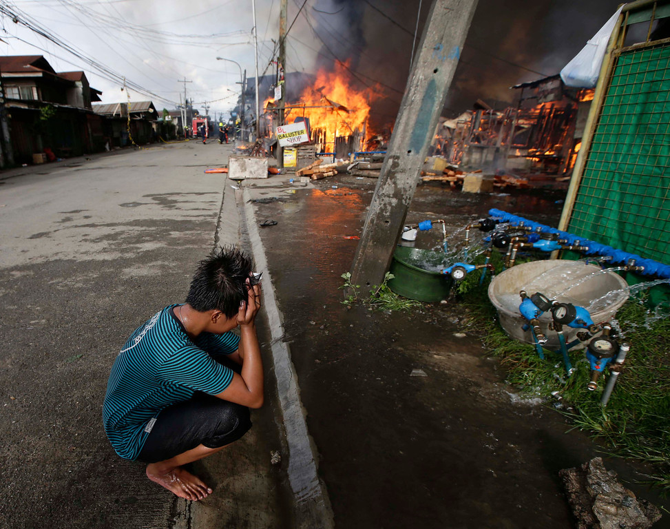 . A resident holds his head as a fire continues to raze several homes while government troopers continue their assault on Muslim rebels Thursday, Sept. 12, 2013, in Zamboanga city in the southern Philippines. The troops have surrounded the Moro National Liberation Front guerrillas with their hostages in four coastal villages since the crisis erupted Monday. (AP Photo/Bullit Marquez)